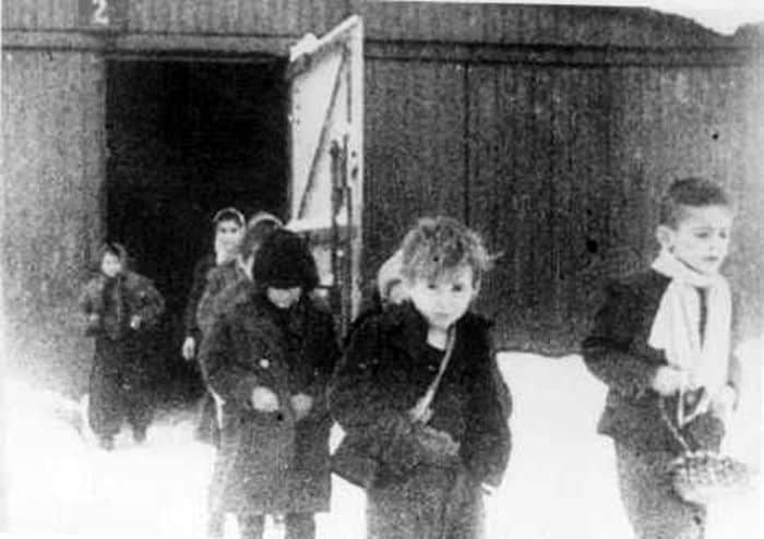 After liberation, surviving children of the Auschwitz camp walk out of the children's barracks. Poland, January 27, 1945