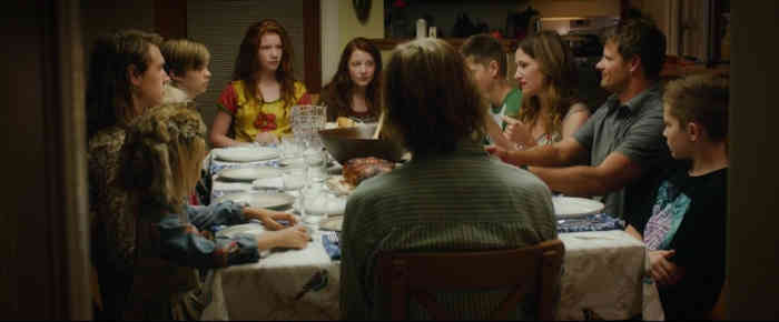 Everyone but the grandparents around a supper table.